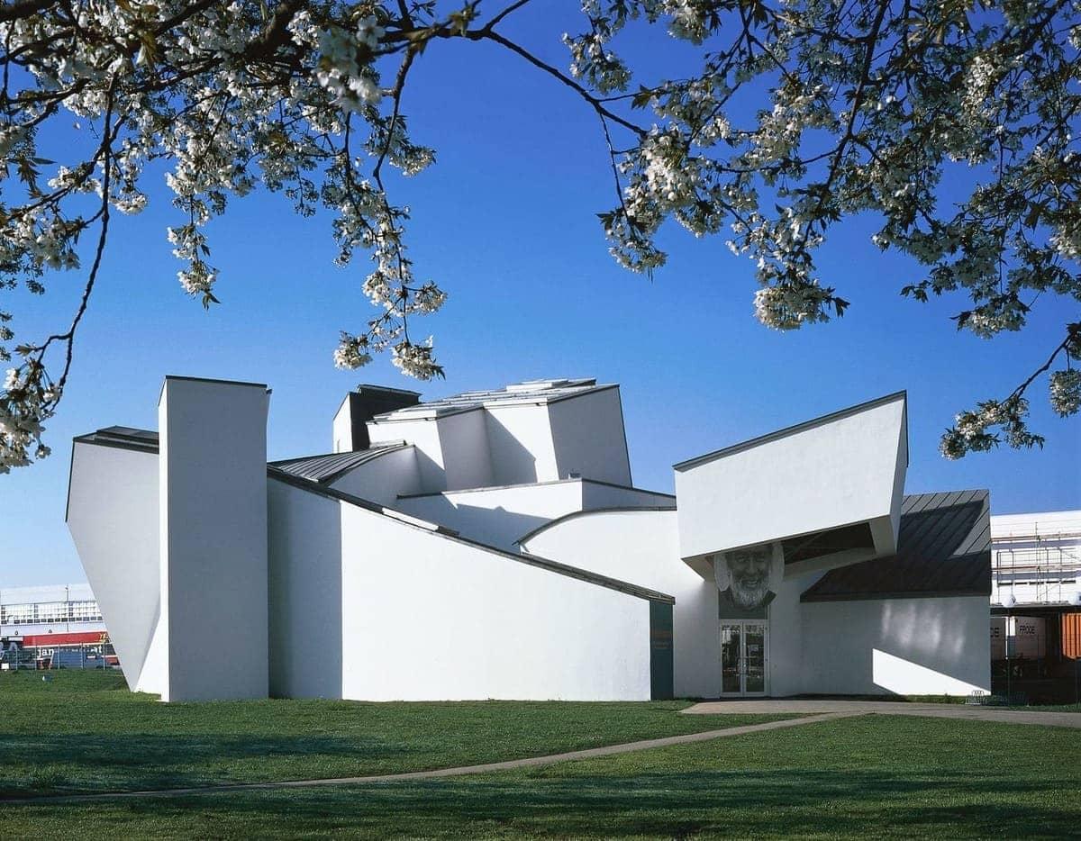 Das Vitra Design Museum von Frank Gehry in Weil am Rhein. Aufgenommen zur Blütezeit eines Kirchbaumes, dessen Blüten sich über die obere Bildhälfte ranken.