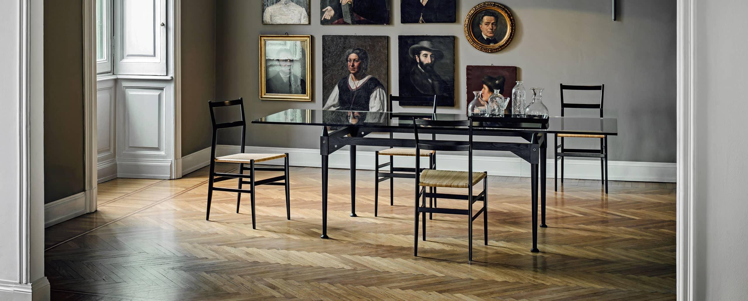 4 Cassina Superleggera Stühle von Gio Ponti in Schwarz an einem Glastisch mit schwarzem Gestell vor einer Portraitbilderwand