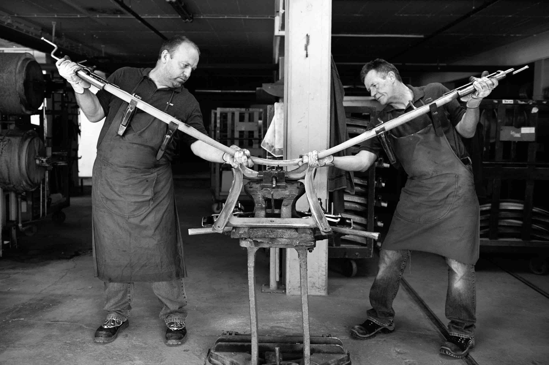 Zwei Mitarbeiter von Thonet biegen Holz für einen Bugholzmöbelstuhl
