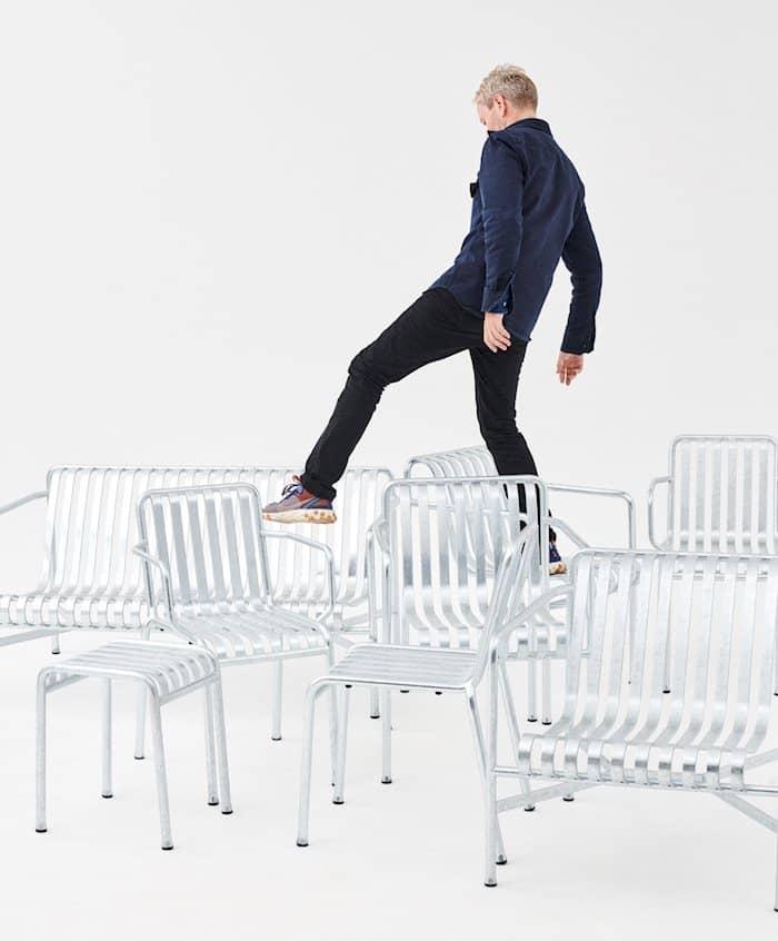 Ein weisser Raum mit Stühlen und Bänken der Outdoormöbel Palisade von den Brüdern Bouroullec. Ronan Bouroullec steht auf einem der Möbel und bewegt sich zu einem anderen.