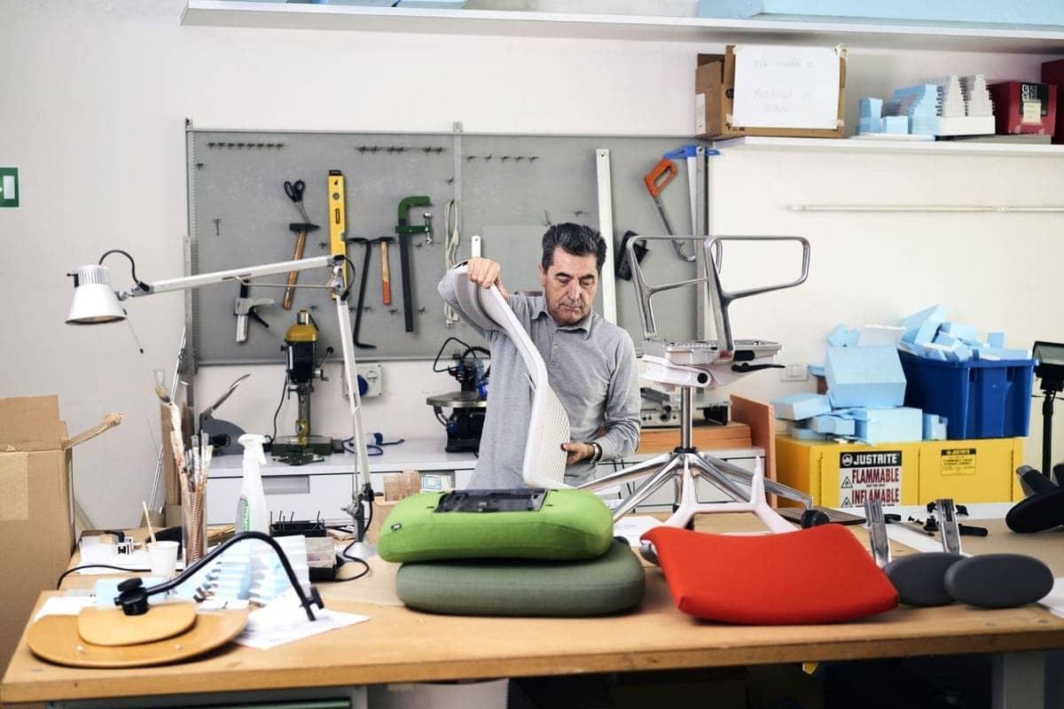 Der Designer Antonio Citterio setzt in einer Werkstatt seinen Vitra ID Bürostuhl zusammen. Neben zwei unterschiedlichen Rückenlehnen für den Stuhl sind auch zwei Armlehnen und Sitzteile sichtbar, die für den Stuhl erhältlich sind.