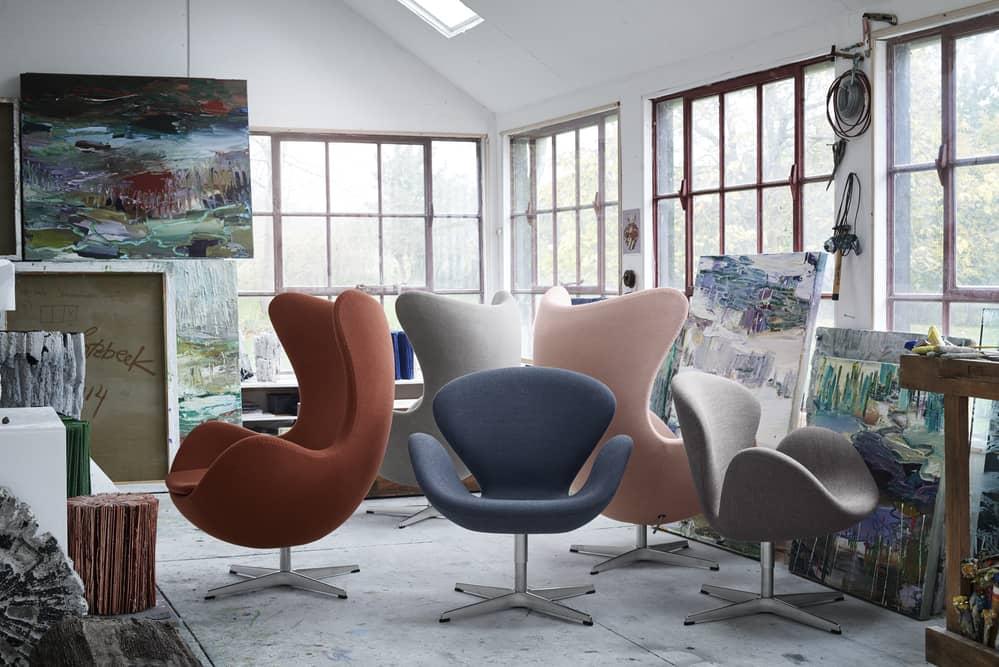 Mehrerer Ei und Schwan Sessel in einem Atelier voller Bilder.
