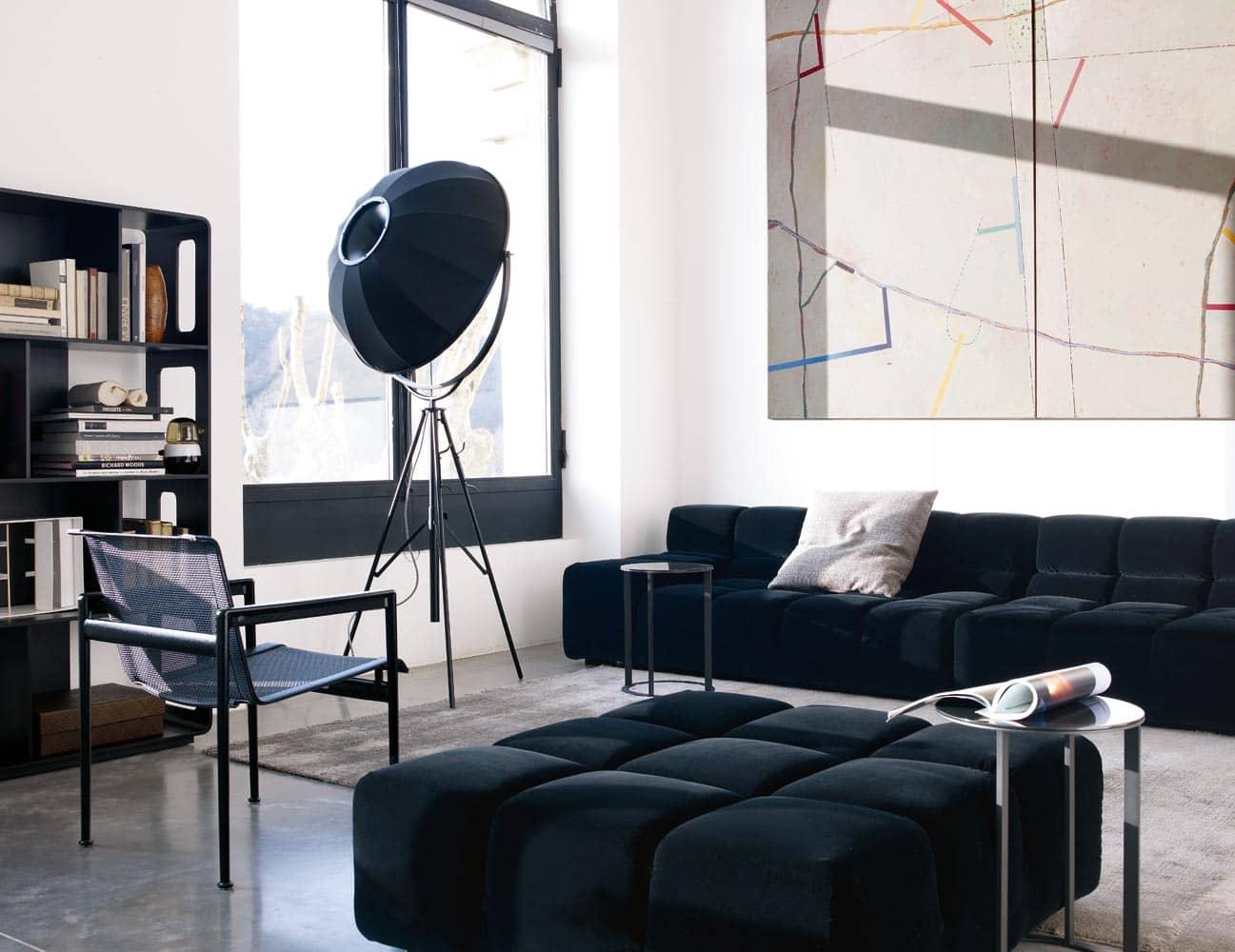 In einer Wohnzimmerecke sieht man zwei Module des Sofas Tufty-Time von Patricia Urquiola für B&B Italia in schwarz vor einem abstrakten Gemälde.