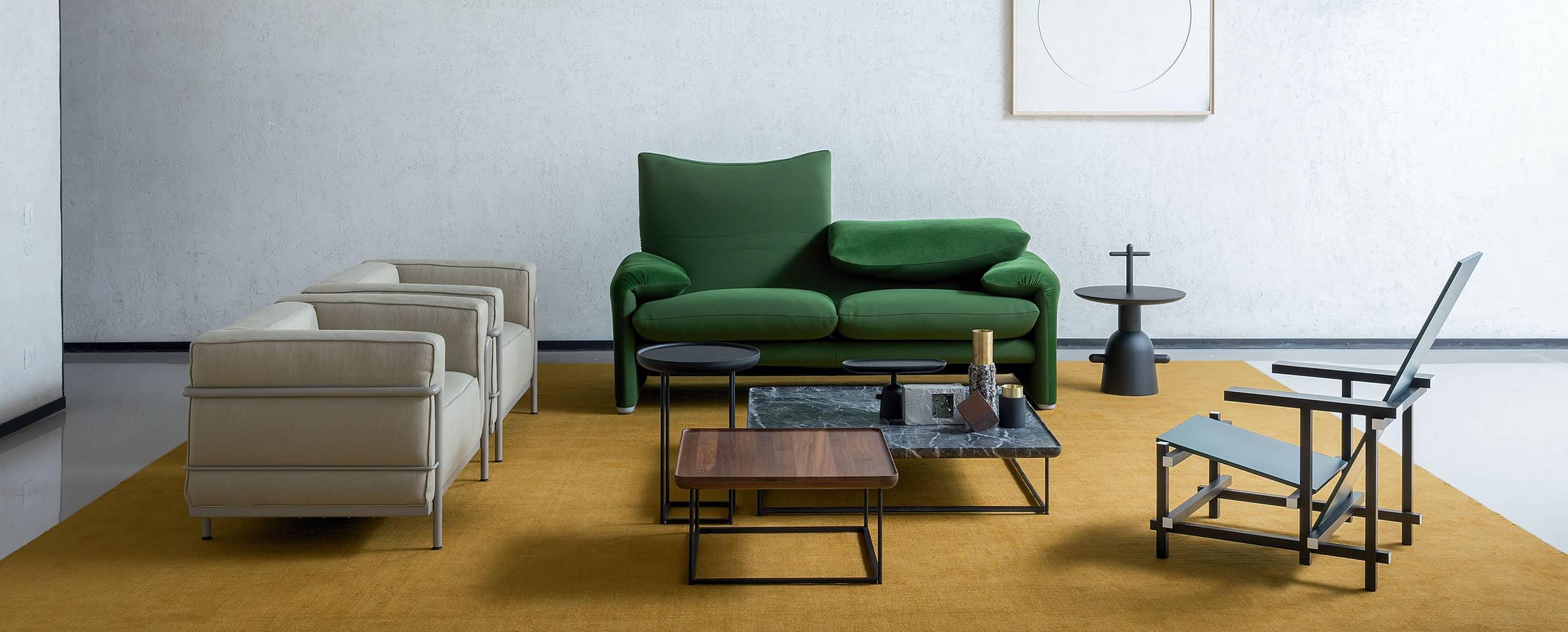 Sitzgruppe auf gelbem Teppich mit grünem Cassina Sofa Maralunga, grauen LC2 Sesseln und Zeilmaker-Version Black-Red-and-Blue