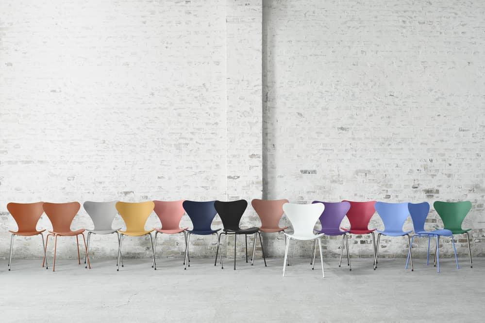 14 Stühle der Fritz Hansen Serie 7 von Arne Jacobsen in vielen Farben vor einer weiss gestrichenen Backsteinwand.