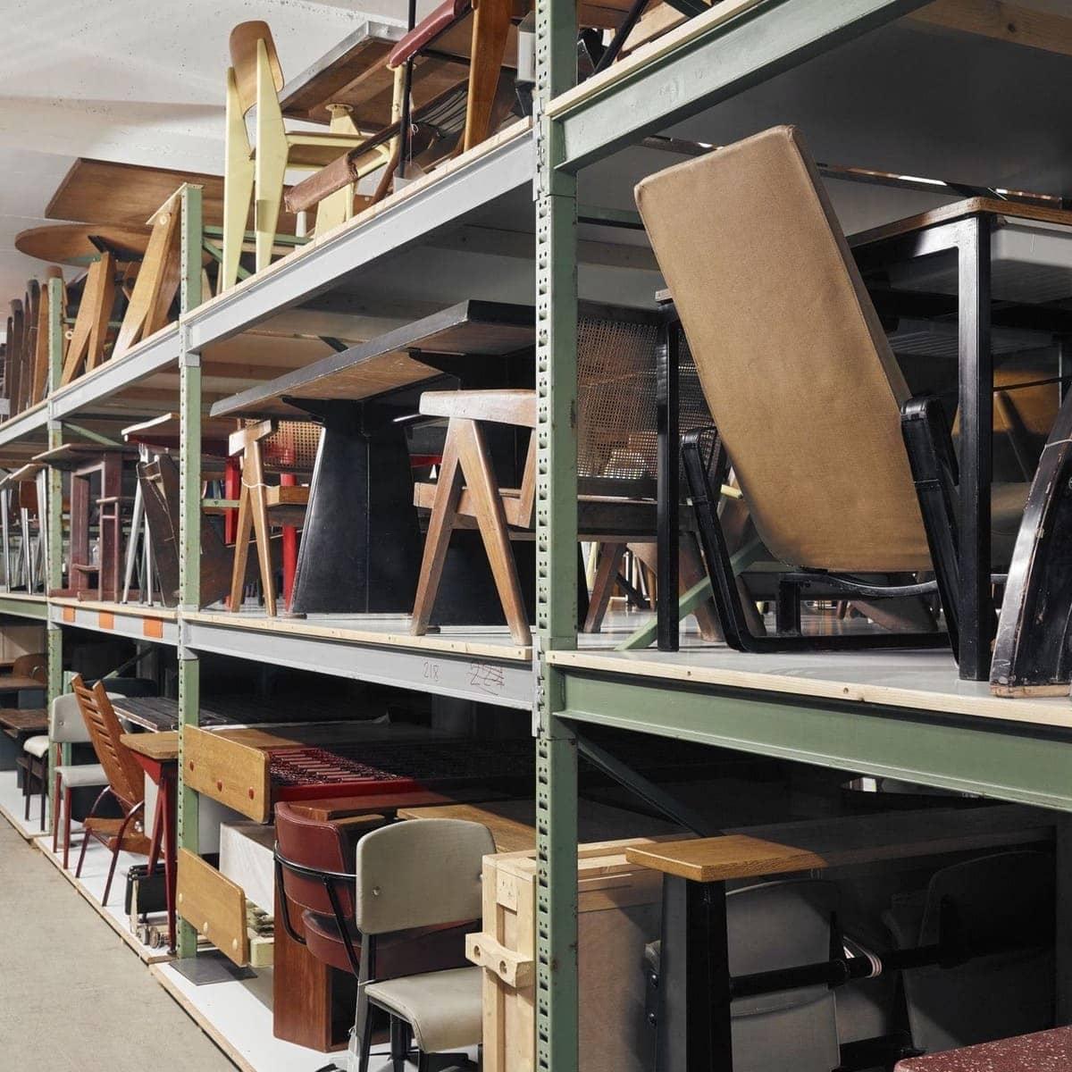 Ein Einblick in die Möbelsammlung des Vitra Design Museum im Untergeschoss des Vitra Schaudepot. Zu sehen sind vornehmlich Stühle, die in einem Lagerregal mit grünen Streben in drei Fächern übereinander gelagert werden. Besonders ins Auge stechen die Standard Stühle von Jean Prouvés.