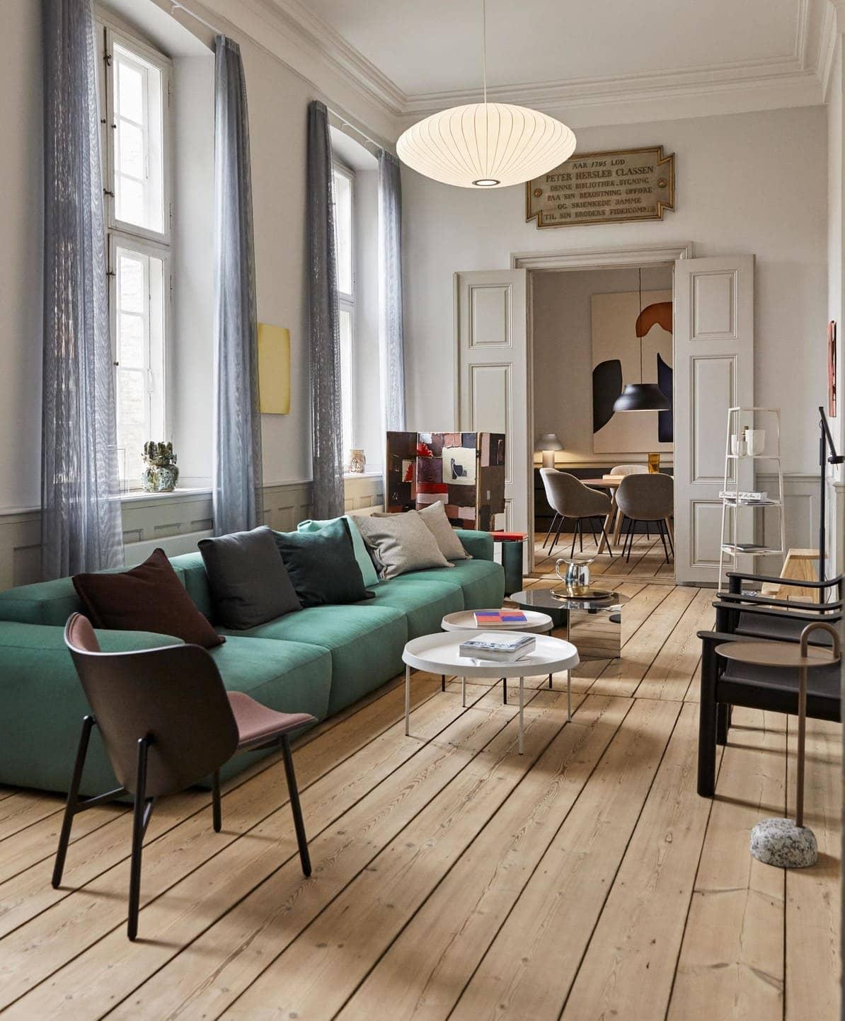 Eine Altbauwohnung mit Holzparkett. Der Blick geht durch das Wohnzimmer mit dem Mags Soft Sofa in Grün von HAY, dem Beistelltisch Slit Hexagon von HAY, dem Beistelltisch Bowler von HAY, auf einen Esstisch mit den HAY Stühlen AAC 27.