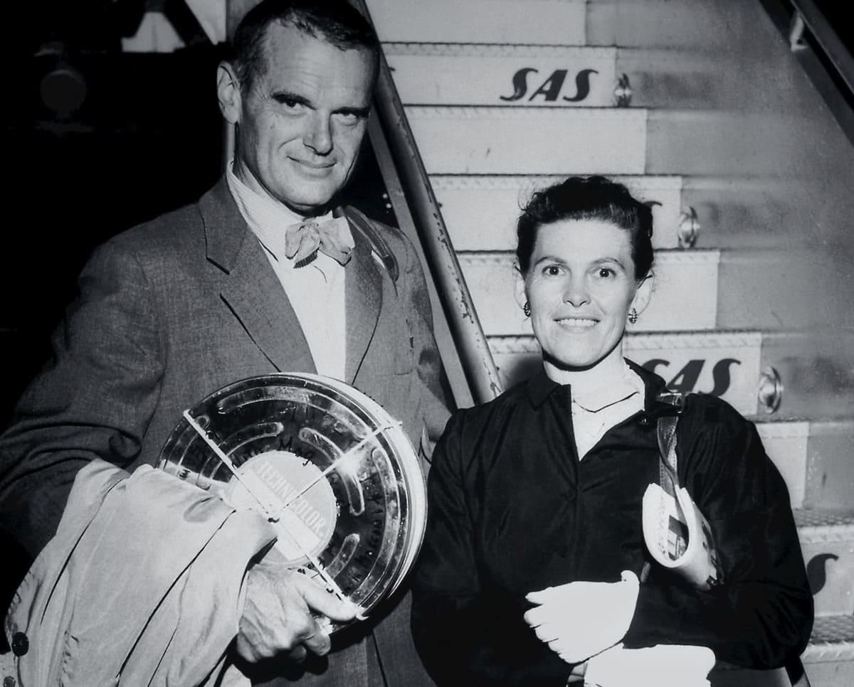 Ein schwarz-weiß Foto von Ray und Charles Eames aus dem Jahr 1959. Es zeigt die beiden mit einer metallenen Filmbox im Arm vor einer Flugzeugtreppe.