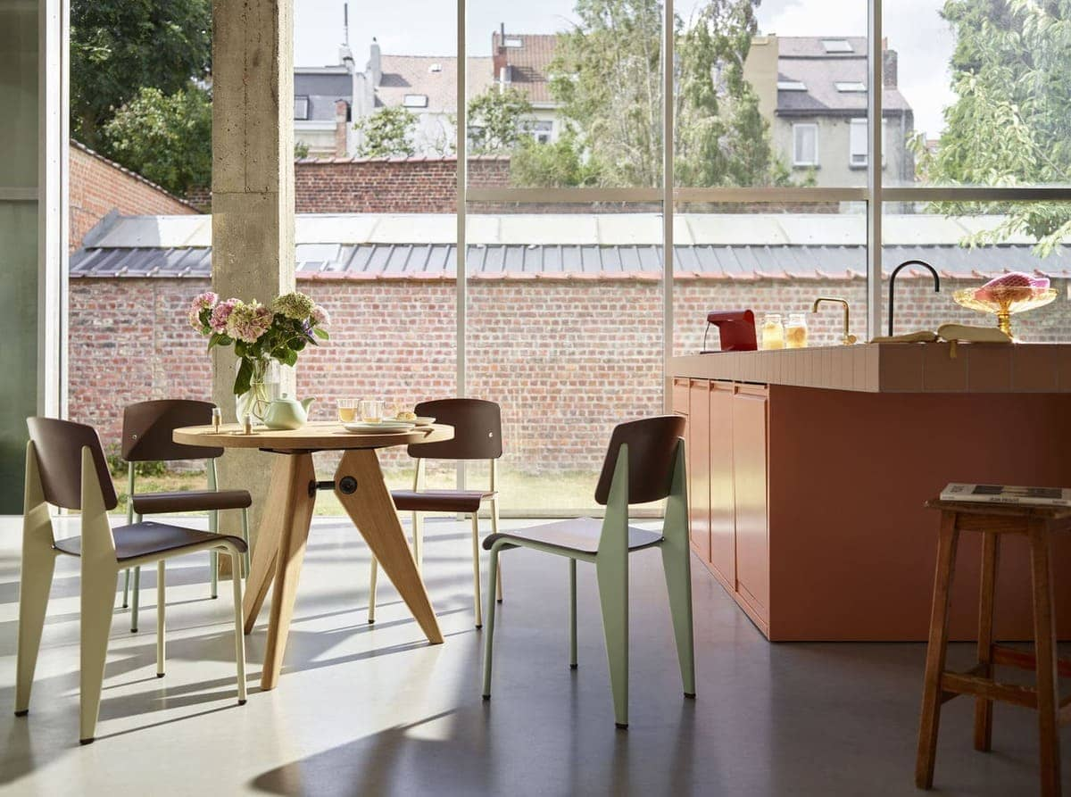 Im Erdgeschoss eines Hauses mit bodentiefen Fenstern steht neben der roséfarbenen Küchenzeile ein runder Vitra Guéridon Tisch mit Standard Stühlen. Beide von Jean Prouvé.